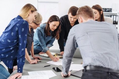 Motivated_group_of_young_business_people_grouped_around_a_table_listening_to_a_female_team_leader_or_manageress_explain_paperwork