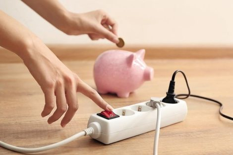 Woman_pressing_a_power_button_of_extension_cord_indoors._Electricity_saving_concept