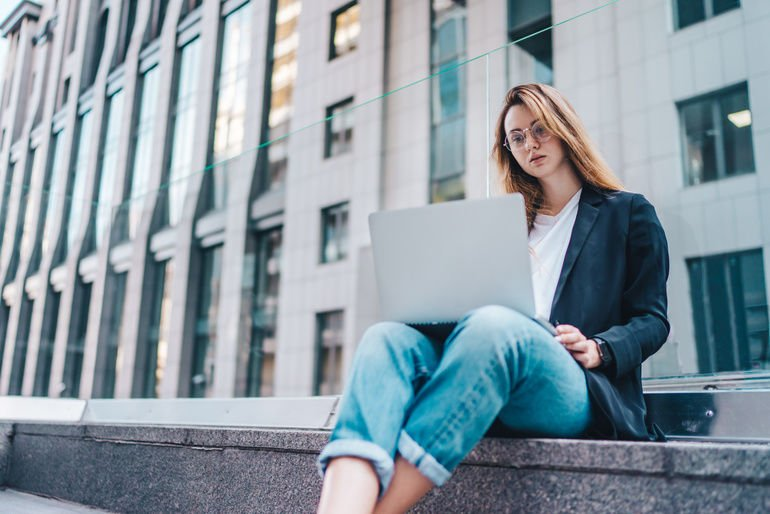 Cute_young_female_entrepreneur_working_on_new_project_using_her_laptop_while_sitting_at_business_center_court.
