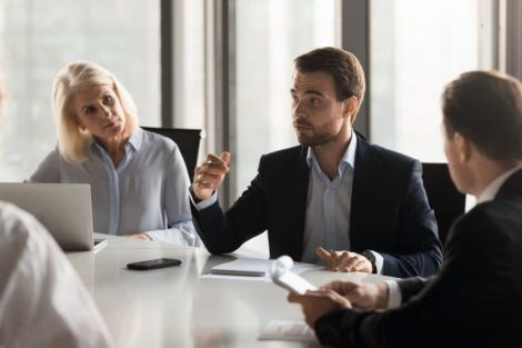 Serious_diverse_colleagues_brainstorm_at_conference_table_discuss_project_at_meeting,_focused_businesspeople_talk_negotiating_in_office_at_briefing,_business_partners_speak_considering_cooperation