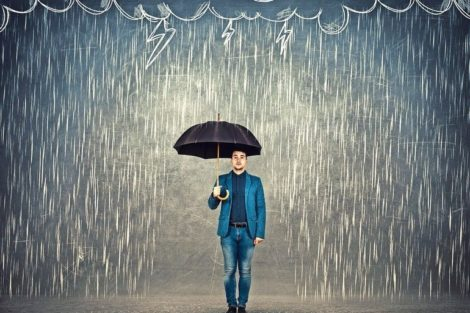 Businessman_standing_under_umbrella_as_protection_of_a_storm_sketch._Insurance_agent,_business_security_concept._Find_solutions_to_escape_crisis_situations.