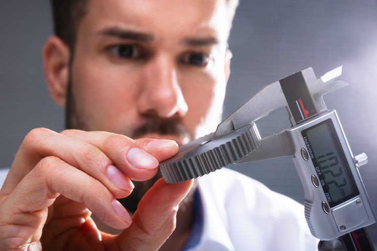Close-up_Of_A_Man's_Hand_Measuring_Gear's_Size_With_Digital_Electronic_Vernier_Caliper