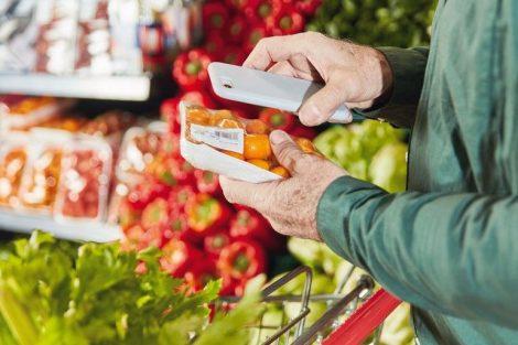 Kunde_scannt_Packung_Lebensmittel_mit_Smartphone_App_zum_Preisvergleich