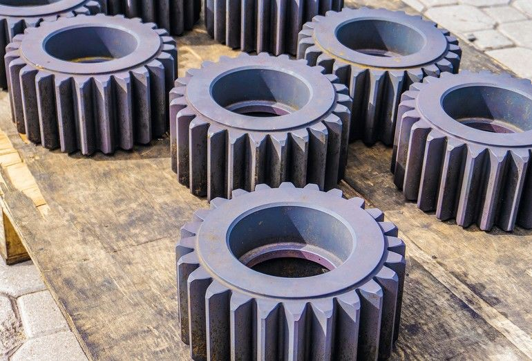 Heat-treated_gears_on_a_wooden_rack,_cool_down_after_quenching_in_an_oven._Gear_cutting_production_concept