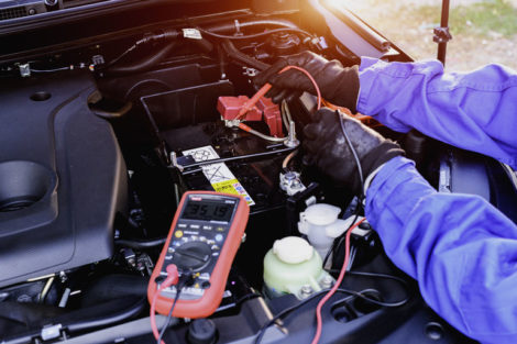 A_technician_measures_the_battery_voltage_in_a_car._Maintenance_and_repair_services