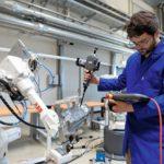 Ein_Mitarbeiter_des_Werkzeugmaschinenlabors_WZL_der_RWTH_Aachen_University_programmiert_in_Aachen_am_Dienstag,_20.Juni_2017,_mit_einem_Tablet_einen_Roboter.