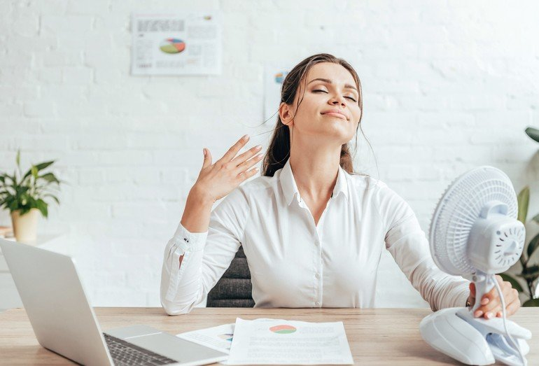 businesswoman_blowing_at_herself_with_electric_fan_while_sitting_at_workplace_with_documents_and_laptop