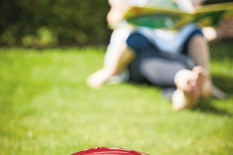 Close-up_of_a_modern_autonomous_mower_on_green_grass_in_front_of_a_young_mother_and_her_child_in_a_sunny_day