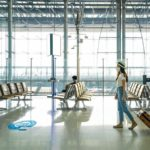 Asian_female_tourist_wearing_mask_walking_in_airport_and_waiting_airline_flight_status_and_keep_distance_in_airport_during_coronavirus_or_covid-19_virus_outbreak_a_new_normal_concept